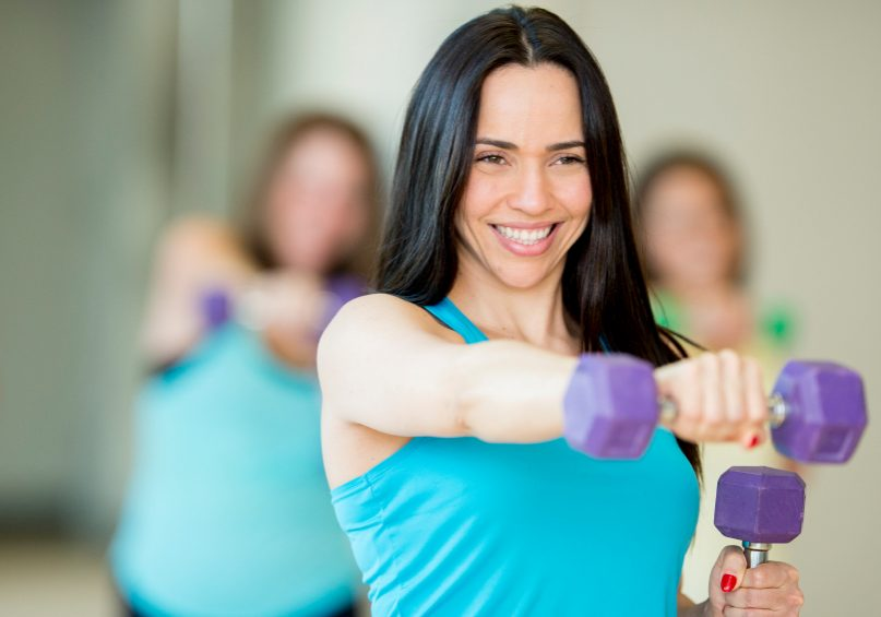 A group of female friends exercising with free weights in a health club, following an instructor.